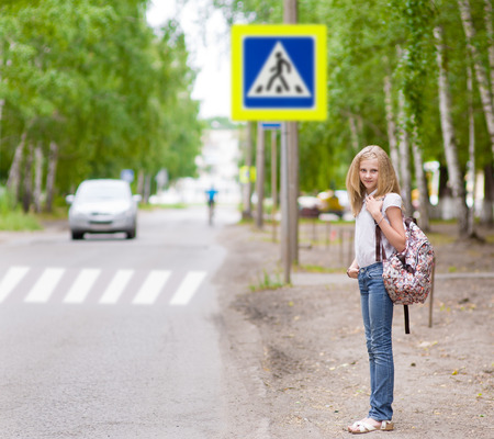 near: teenager standing  girl near the pedestrian crossing