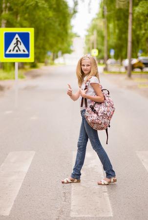 paso de peatones: chica adolescente que muestra los pulgares para arriba en el paso de peatones