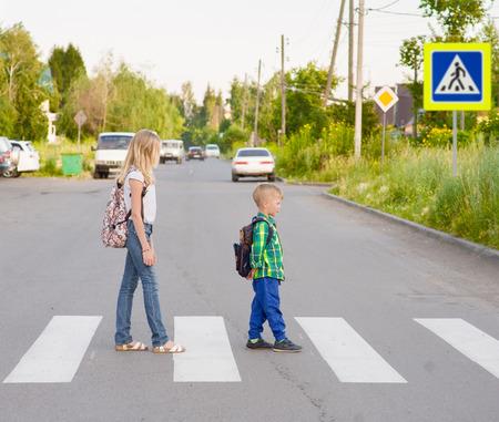 kinderen lopen op het zebrapad