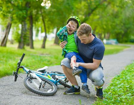 Padre inspecciona el niño herido se había caído de la moto Foto de archivo - 45040697