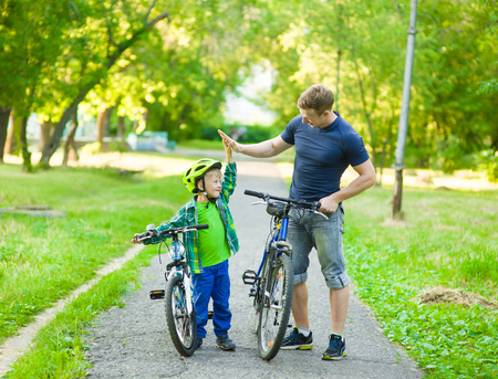 cycle ride: father and son give high five while cycling in the park