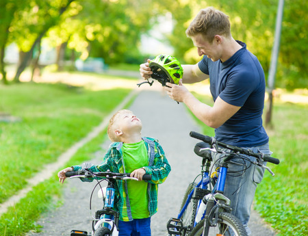 a helmet: young father trying to wear a bicycle helmet to his son