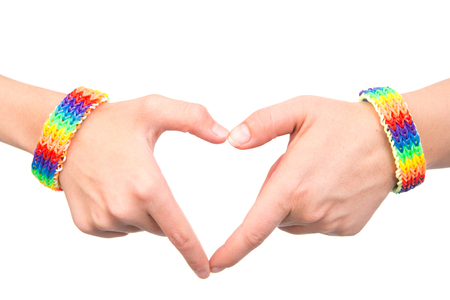 sex discrimination: Female hands with a bracelet patterned as the rainbow flag showing heart sign.
