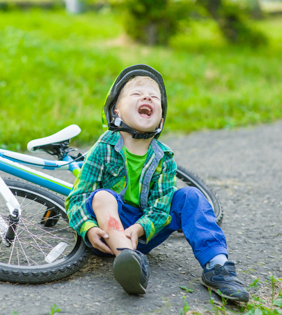 Children cry: boy fell from the bike in a park.
