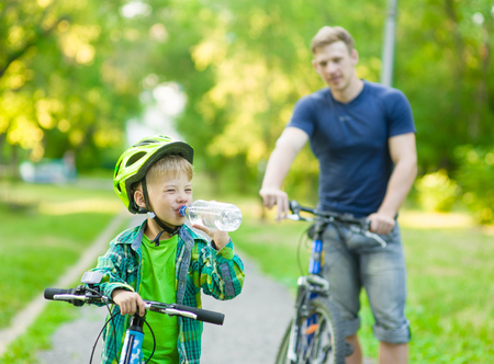 water vehicle: Little boy drinking water by the bike. Stock Photo