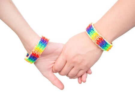 sex discrimination: Closeup hands with a bracelet patterned as the rainbow flag. isolated on white background. Stock Photo