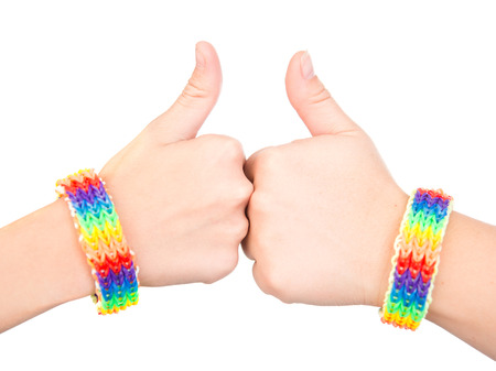 sex discrimination: Female hands with a bracelet patterned as the rainbow flag showing thumbs up. isolated on white background.
