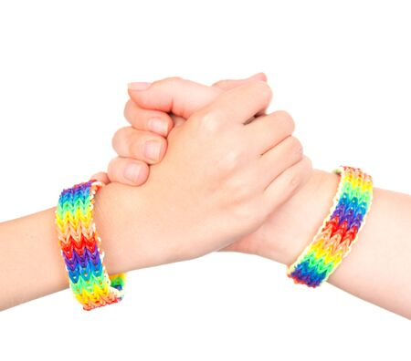 sex discrimination: young girls shaking hands with a bracelet patterned as the rainbow flag. isolated on white background.