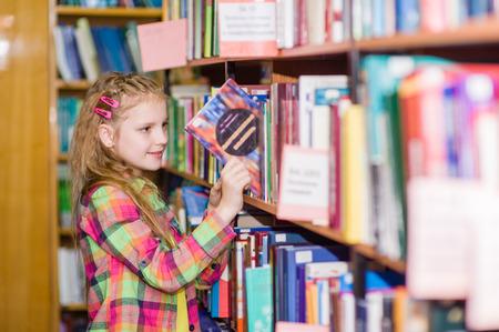 escuela primaria: niña escoge un libro en la biblioteca.
