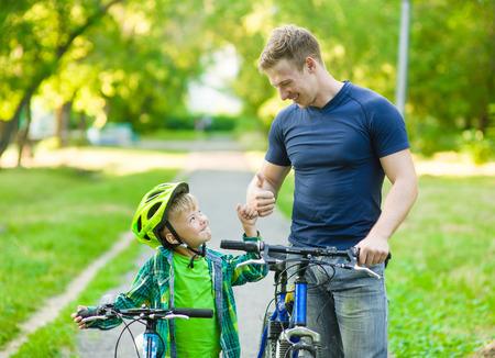 vader die met zijn zoon een fiets rijden en het tonen van duim omhoog. Stockfoto