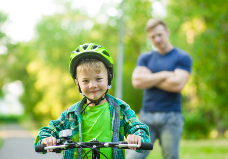 weekend activities: child on a bicycle with father in the park.