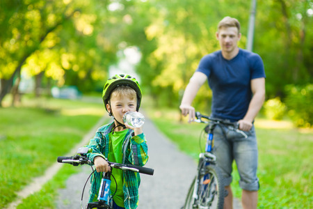 sports training: young boy with a bottle of water is learning to ride a bike with his father.