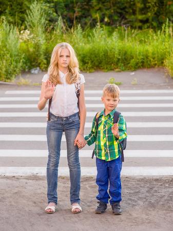 open palm: Children stand near a pedestrian crossing and show an open palm. Stock Photo