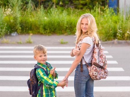 子供は、横断歩道や親指を出て近くに立ちます。