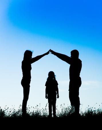 silhouette maison: Silhouette d'une famille heureuse en faisant le signe de la maison.