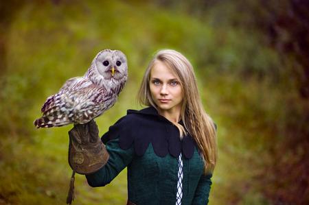 medieval dress: chica en traje medieval es la celebraci�n de un b�ho en su brazo.