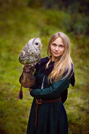 medieval dress: mujer joven en traje medieval con un b�ho en su brazo.