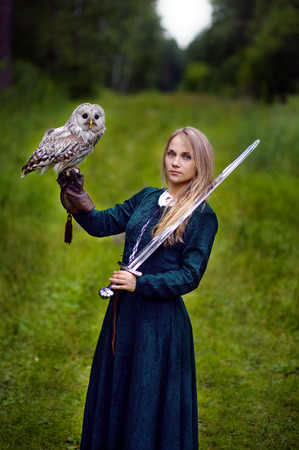 girl with sword holding an owl on her arm. Stock Photo