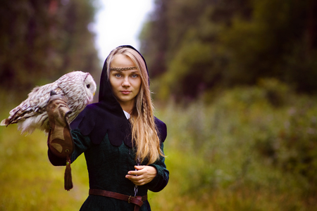 young woman in medieval dress with an owl on her arm.