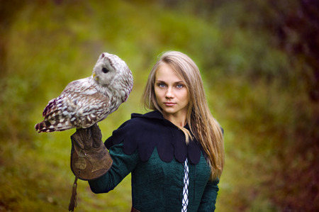 vestido medieval: chica en traje medieval es la celebración de un búho en su brazo.