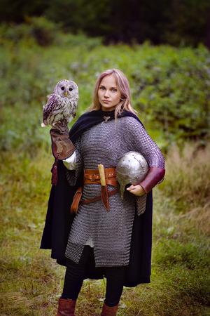 edad media: chica en una armadura medieval, la celebración de un búho