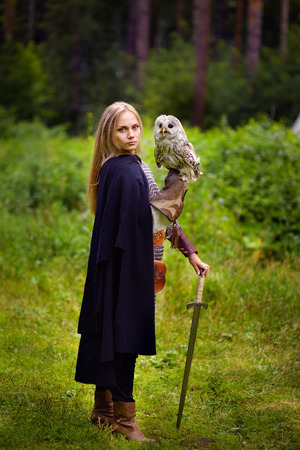 warrior woman: girl in armor and with a sword holding an owl.