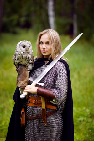 historical: girl in armor and with a sword holding an owl.