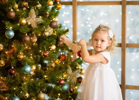 new baby: Little girl decorates the Christmas tree.