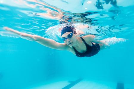 Female swimmer gushing through water in pool.