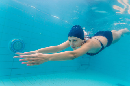Woman swimming underwater in pool. Imagens
