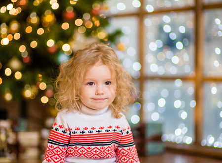 clothes winter: Portrait of blonde girl on the background of Christmas tree.