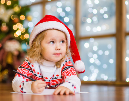 writes: Little girl in red christmas hat writes letter to Santa Claus.