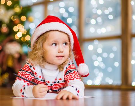 Menina no chapéu vermelho do Natal escreve carta para Papai Noel.