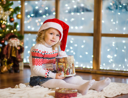 baby open present: Little girl in red santa hat with gift box.