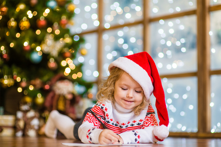 Little girl in Santa hat writes letter to Santa Claus.