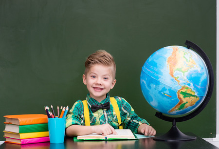 looking to camera: Portrait of a happy boy in classroom. Stock Photo