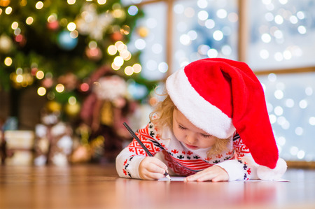 Little girl in red christmas hat writes letter to Santa Claus.