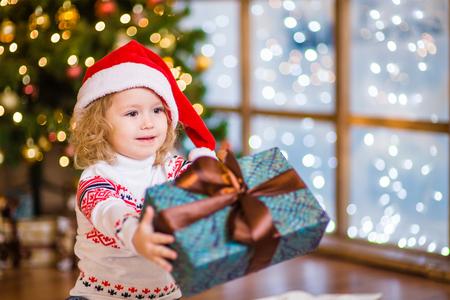 dar un regalo: La muchacha en el sombrero rojo de santa que presenta un regalo. Foto de archivo