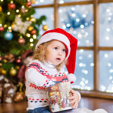 baby open present: Young girl in red santa hat opening Christmas gifts.