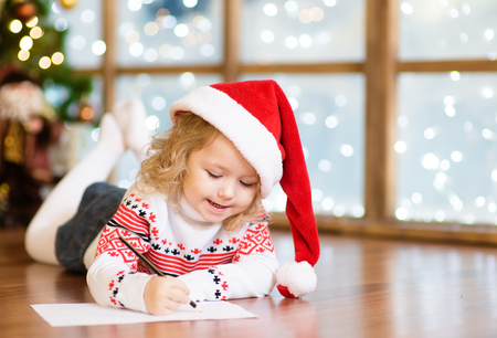 Happy girl in a red Christmas hat writing a letter to Santa Claus.