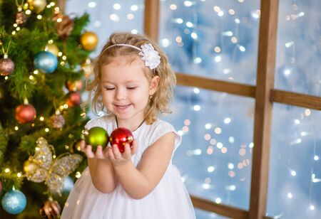 Little girl holding a Christmas toy.
