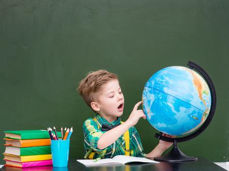 exploring: Young boy exploring the globe. Stock Photo
