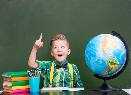 little finger: Surprised boy in classroom. Stock Photo