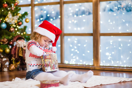 christmas hat: Little girl in red christmas hat with gift box.