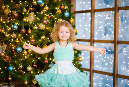 new year tree: Girl spread her arms to the side near the Christmas tree.