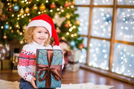 baby near christmas tree: Baby girl in red santa hat holding big gift box near the Christmas tree.