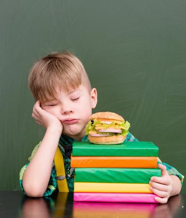 child sad: Boy asleep on a pile of books near empty chalkboard.