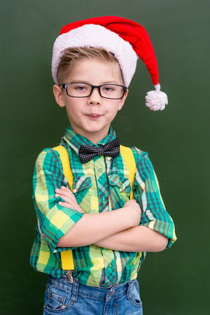 christmas hat: Portrait of a boy in the Christmas cap near a school board. Stock Photo