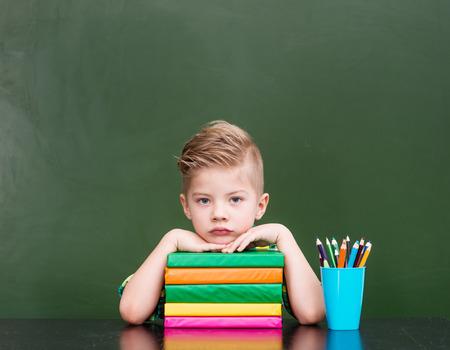 Tired schoolboy in classroom.