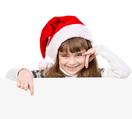 billboard background: Happy Christmas girl with santa hat points down. isolated on white background.